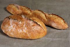 Dos panes blancos de diversas formas mienten en el tablec de lino gris Foto de archivo libre de regalías