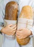 Dos panes de pan fresco del trigo y de centeno en manos del ` s de los niños Foto de archivo