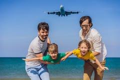Dos papás y dos hijos se divierten en la playa que miran los aviones de aterrizaje El viajar en un aeroplano con concepto de los  imagen de archivo