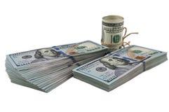 Dos paquetes de cientos billetes de dólar y un rollo de los dólares atados con una cuerda en un fondo blanco Visión en ángulo foto de archivo libre de regalías