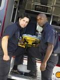 Dos paramédicos que quitan la camilla de la ambulancia fotos de archivo libres de regalías
