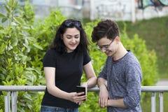 Dos pares adolescentes lindos que se colocan en el patio de escuela y la mirada Fotografía de archivo libre de regalías