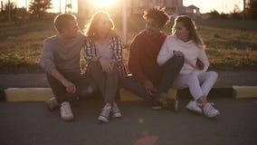 Dos pares competidos con mezclados de los jóvenes se sientan en el encintado en la calle Sonriendo, outdors felices de la gente j almacen de video