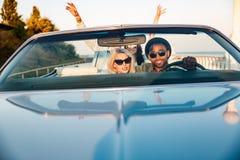 Dos pares con las manos aumentadas en el coche Fotos de archivo