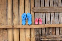Dos pares de chancletas en vacaciones de verano de la pared que esperan de madera para fotos de archivo