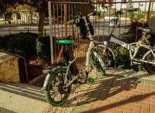 Dos pares de las bicicletas - una de ellas eléctricas, encadenado para metal la cerca, pasos cercanos que van abajo a la calle Imágenes de archivo libres de regalías
