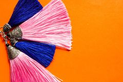 Dos pares de pendientes azules y rosados de la borla mienten en un círculo en el fondo anaranjado fotografía de archivo