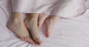 Dos pares de piernas de la familia en cama debajo de la sobrecama - madre y beb? imagen de archivo libre de regalías