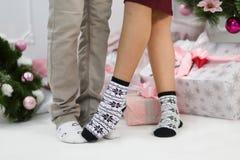 Dos pares de piernas masculinas y femeninas en calcetines con los modelos de los pingüinos y de los copos de nieve interiores Foto de archivo libre de regalías