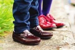 Dos pares de pies de los niños que llevan los zapatos de la moda Imágenes de archivo libres de regalías