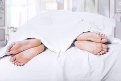 Dos pares de pies en cama Imagen de archivo libre de regalías
