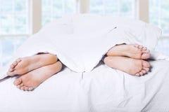 Dos pares de pies en la cama 1 Imagenes de archivo