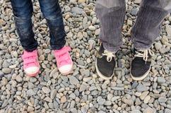 Dos pares de pies en las zapatillas de deporte, adultos y niños, están en el guijarro Imágenes de archivo libres de regalías