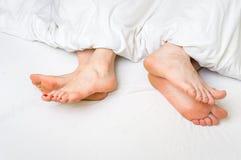 Dos pares de pies lejos de uno a en una cama Imagen de archivo libre de regalías