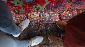 Dos pares de pies que pisan la pintura en la pared metrajes