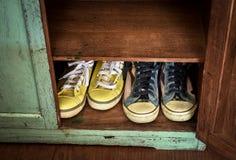 Dos pares de zapatillas de deporte en el gabinete Imagen de archivo