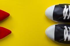 Dos pares de zapatos opuestos en fondo amarillo Imagen de archivo
