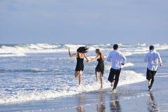 Dos pares, divirtiéndose en una playa Fotos de archivo libres de regalías