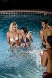 Dos pares en piscina en la noche Fotos de archivo libres de regalías