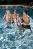 Dos pares en piscina en la noche Fotografía de archivo