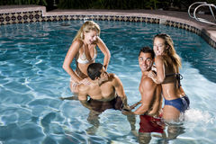 Dos pares en piscina en la noche Imagenes de archivo