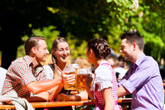 Dos pares felices que se sientan en jardín de la cerveza Imagen de archivo libre de regalías