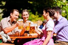 Dos pares felices que se sientan en jardín de la cerveza Fotos de archivo libres de regalías