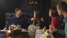 Dos pares hermosos comunican activamente en el restaurante y esperar su orden metrajes
