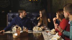 Dos pares hermosos comunican activamente en el restaurante y esperar su orden almacen de metraje de vídeo