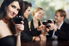 Dos pares jovenes con los vidrios de vino rojo en la celebración o el partido Imagen de archivo