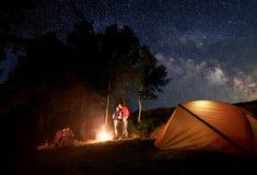 Dos pares jovenes en la hoguera debajo del cielo estrellado brillante cerca de la tienda en el fondo de árboles imagenes de archivo