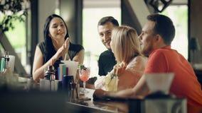 Dos pares jovenes que beben los cócteles en el contador de la barra Cuatro estudiantes que pasan el tiempo juntos que celebra día metrajes