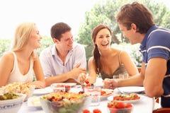 Dos pares jovenes que comen al aire libre Imágenes de archivo libres de regalías