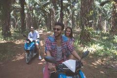 Dos pares jovenes que conducen la vespa en el viaje por carretera tropical de Forest Cheerful Friends Group Enjoy junto Fotos de archivo