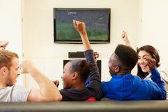 Dos pares jovenes que miran la televisión en casa junto Imagen de archivo