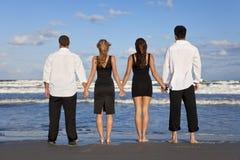 Dos pares, llevando a cabo las manos en una playa Imagen de archivo