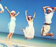 Dos pares que celebran concepto del verano de la Navidad de la playa Foto de archivo