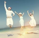 Dos pares que celebran en la playa en concepto de la Navidad Imágenes de archivo libres de regalías