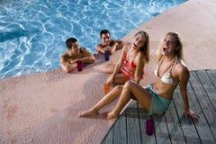Dos pares que cuelgan hacia fuera en cubierta de la piscina Fotos de archivo libres de regalías