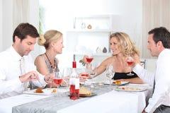 Dos pares que disfrutan de la comida Foto de archivo libre de regalías