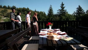 Dos pares que miran la hermosa vista de la naturaleza antes de comer el almuerzo de cortes fríos almacen de video