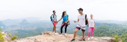 Dos pares turísticos con la mochila en hablar superior de la montaña sobre la opinión hermosa del panorama del paisaje imagen de archivo