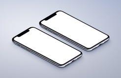 Dos partes delanteras de la maqueta de los smartphones de la perspectiva que mienten en superficie gris Fotos de archivo libres de regalías