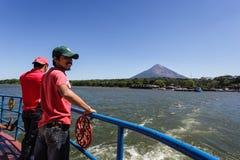 Dos pasajeros se colocan en el carril durante paseo del transbordador a la isla de Ometepe en el lago Nicaragua. Imagen de archivo