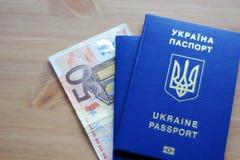 Dos pasaportes biométricos ucranianos con el billete de banco de cincuenta euros fotografía de archivo
