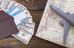 Dos pasaportes extranjeros con los billetes de dólar incluidos con una tarjeta turística y un aeroplano Fotografía de archivo