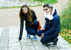 Dos paseos de las muchachas en parque del otoño Foto de archivo libre de regalías