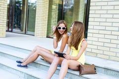 Dos pasos de las hermanas de la risa del instituto feliz mirando una tableta en vidrios sociales de las redes, resto, moda de la  Imagen de archivo libre de regalías