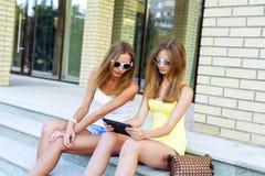 Dos pasos de las hermanas del instituto que mira una película en la tableta en redes sociales, con los vidrios y los pantalones c Fotografía de archivo