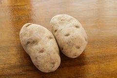 Dos patatas que cuecen en la tabla de madera Imagenes de archivo